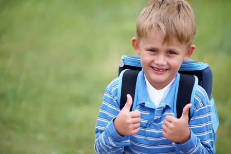 portrait of happy schoolboy with satchel on his back photo