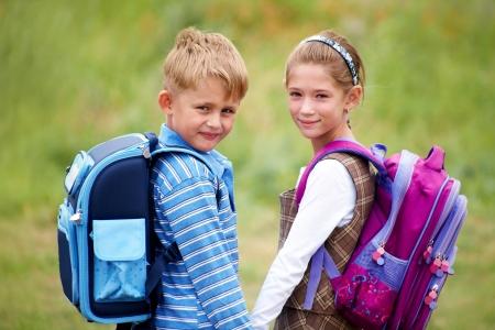 school bag: Ritratto di ragazzo con la ragazza a scuola a piedi insieme a rantsemi dietro