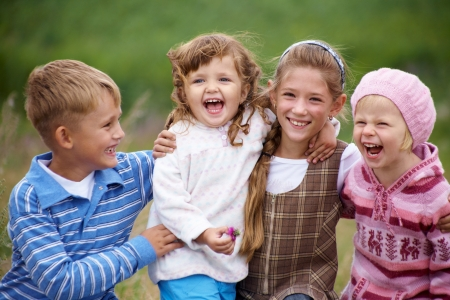 people laughing: portrait of a group of children happily laughing and playing on the grass