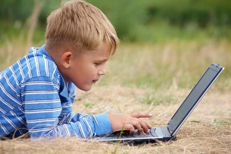 lying in grass: ni�o acostado hierba escribe una carta en la computadora port�til Foto de archivo