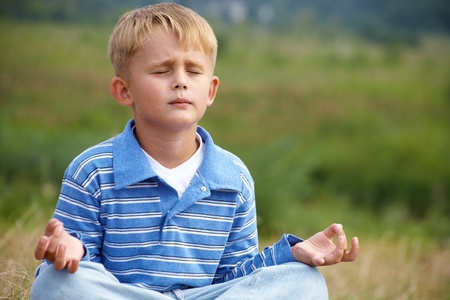 meditating: little boy is meditating in the lotus position on a background of green meadows