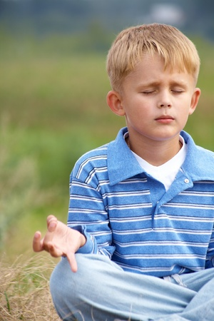 little boy is meditating in the lotus position on a background of green meadows photo
