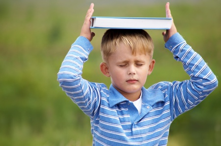 meditates: schoolboy meditates on the head with  book on the background of green meadows