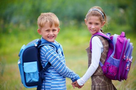 school bag: Retrato de niño con la chica caminando a la escuela junto con rantsemi detrás