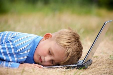 niños pensando: niño se quedó dormido en la computadora portátil en el césped Foto de archivo