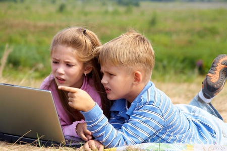 boy and girl lying on the lawn and do on your laptop Stock Photo - 10872132