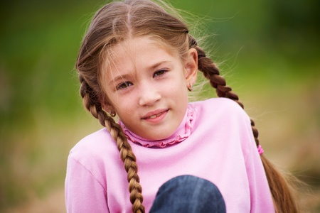 pink posing: portrait of little girl with pigtails smiling at the camera against  background of green