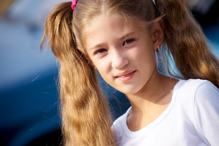 colegiala: Retrato de niña con el pelo largo, sonriendo a la cámara el azul Foto de archivo