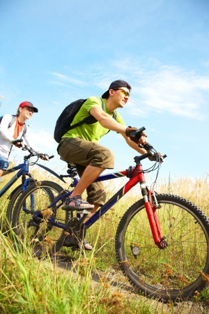 Couple of cyclists riding bicycles in countryside Stock Photo - 10664861