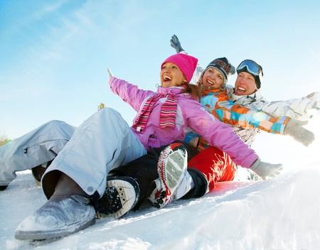 winter couple: Group of  teenagers slide downhill in wintertime Stock Photo