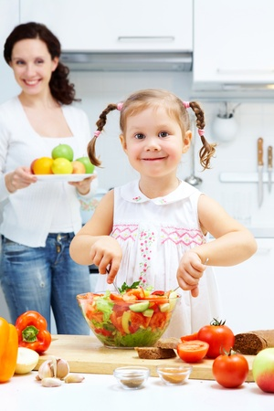 Happy girl mixing salad in bowl while woman holding plate full of fruits in the background photo