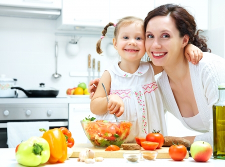 Mother and daughter cooking dinner in kitchen  photo