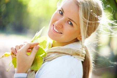 femmes souriantes: Portrait d'une belle femme blonde à l'automne parc Banque d'images