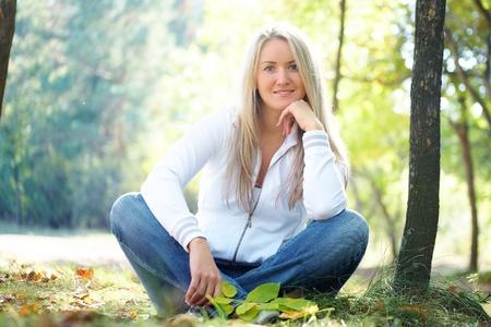 Portrait of a beautiful blonde woman in autumn park photo