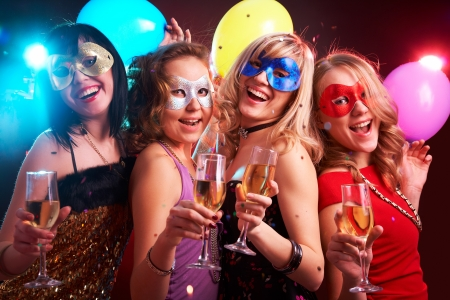 female mask: Portrait of happy young girls under masks on the party Stock Photo