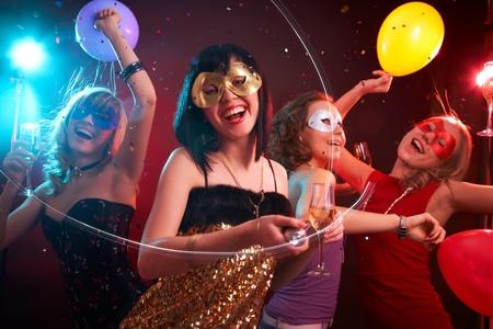 femme masqu�e: Danse heureuse de jeunes filles sous les masques � la partie Banque d'images