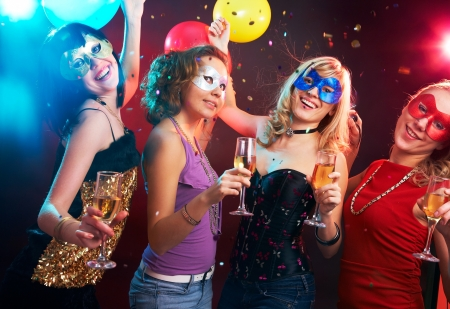 masquerade masks: Portrait of happy young girls under masks on the party Stock Photo