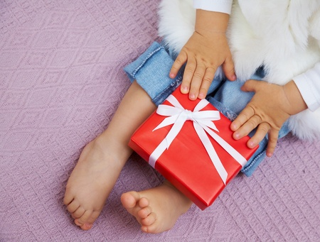 small child holds a nice Christmas present on her knees photo