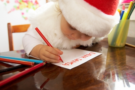 The small child writes the letter to Santa photo