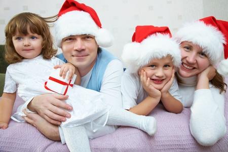 Die gl�ckliche Familie mit zwei kleinen Kindern in Weihnachten Kappen freut sich zusammen