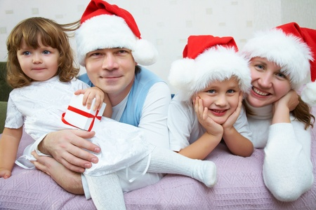 rejoices: The happy family with two small children in Christmas caps rejoices together