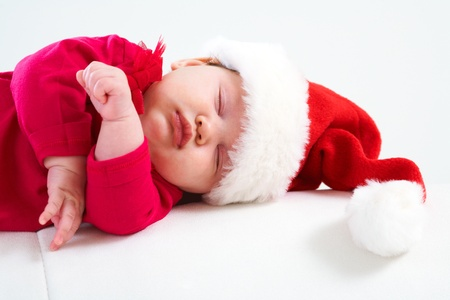 Cute baby in Santa hat sleeping in Christmas night photo