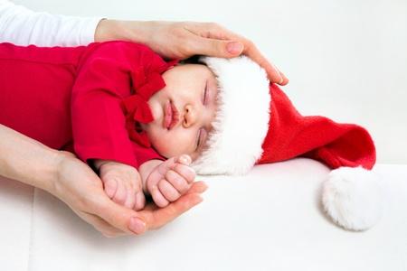 baby s: Cute baby in Santa hat sleeping in mother�s hands