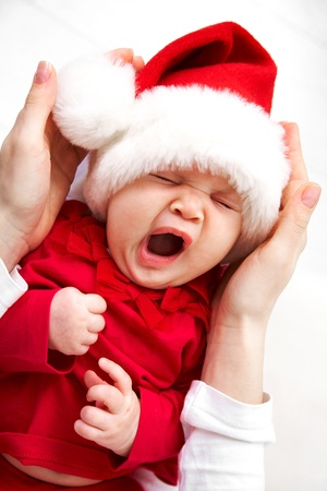 Cute baby in Santa hat sleeping in mother�s hands photo