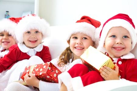 cappello natale: Gruppo di quattro figli in cappello di Natale con regali