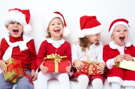 baby kerst: Groep van vier kinderen in de kerstmuts met cadeautjes