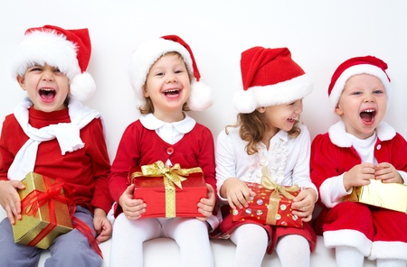 children party: Group of four children in Christmas hat with presents Stock Photo
