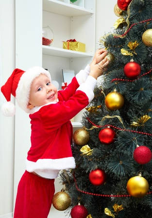 Cute little boy decorating Christmas tree photo