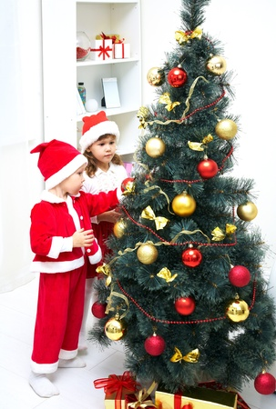 Cute little boy and girl decorating Christmas tree