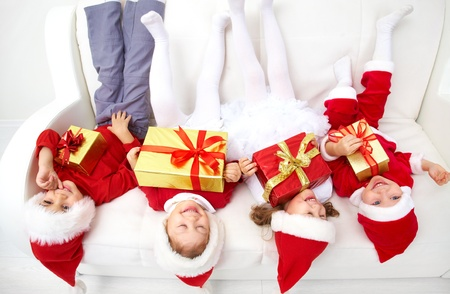 four month: Group of four children in Christmas hat on sofa head over heels