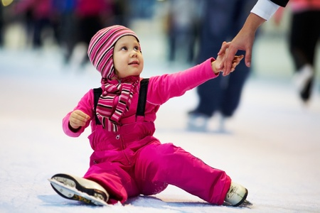 figure skating: Mother�s hand help little cute girl on the rink