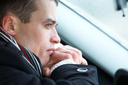 uneasiness: Retrato de hombre atractivo en el coche en invierno