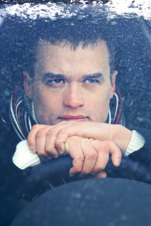 uneasiness: Portrait of attractive man in car in winter time