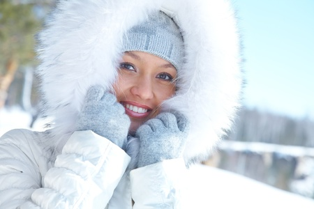 seasonal clothes: Portrait of young woman in white fur in winter