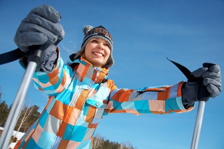 snow ski: Portrait of young woman skier on blue sky background