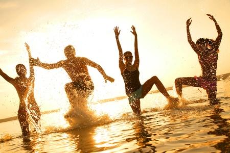 grupo de jovens felizes que dançam na praia no por do sol bonito do verão Imagens