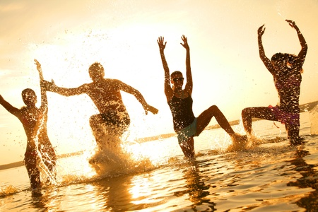 čtyři lidé: Skupina happy mladých lidí tančí na pláži na krásnou letní západ slunce