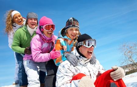 Gruppe von Jugendlichen Rutsche bergab im Winter