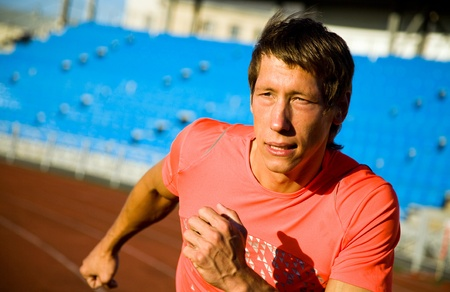 young muscular athlete is running of the treadmill at the stadium photo