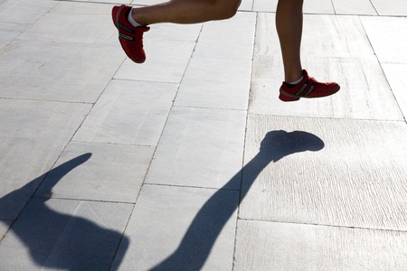 foots of running man and shadow Stock Photo