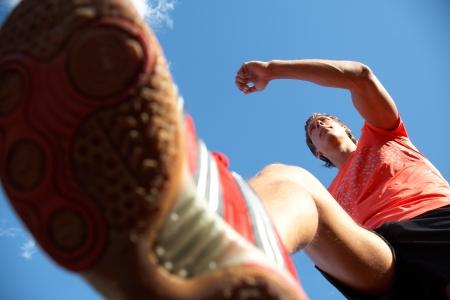 ropa deportiva: joven corriendo levantando los pies de alto sobre el cielo azul. Vista desde abajo Foto de archivo