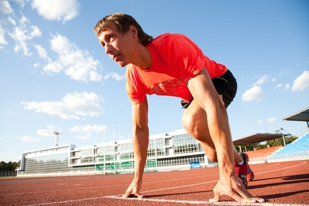 starting line: young man runs through the stadium and look back