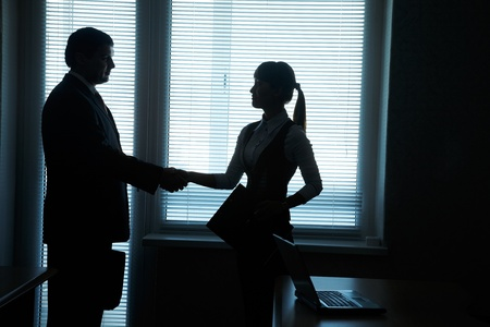 back to work: silhouettes of business partners handshake against the window in the office