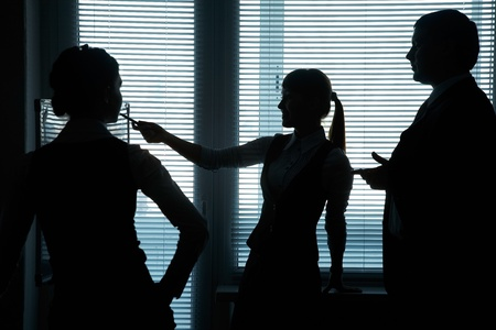 silhouettes of business partners discuss against the window in the office photo