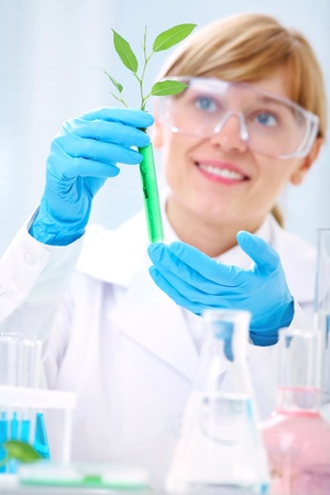 Woman scientist holding a test tube with plant. Ecology photo