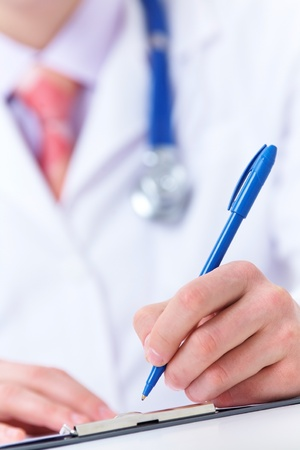 prognosis: Clouse-up of doctor writing down prognosis on medical chart  Stock Photo